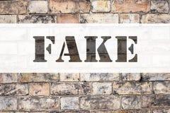 显示假新闻的概念性公告文本说明启发 在老砖背景写的假新闻的企业概念 免版税库存照片