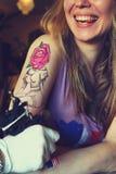 显示做的Tattooer纹身花刺的过程在年轻美丽的行家妇女 库存图片