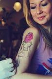 显示做的Tattooer纹身花刺的过程在年轻美丽的行家妇女 免版税库存照片