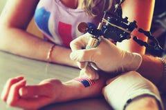 显示做的Tattooer纹身花刺的过程在年轻美丽的行家妇女 免版税图库摄影