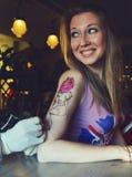 显示做的Tattooer纹身花刺的过程在年轻美丽的行家妇女 库存照片