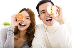 显示健康食物的愉快的年轻夫妇 免版税图库摄影