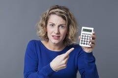 显示充满愤怒的不快乐的20s女孩一个计算器 免版税库存图片