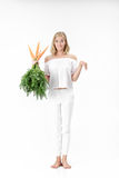 显示兔子和拿着与绿色叶子的美丽的白肤金发的妇女新鲜的红萝卜在白色背景 饮食健康 库存图片
