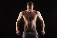 显示六块肌肉吸收的运动英俊的人健身模型 隔绝在与Copyspace的黑背景 免版税库存图片