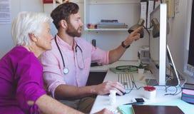 显示关于计算机的男性医生医疗报告在诊所屋子 库存照片