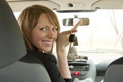 显示关键字的汽车的愉快的女孩 免版税库存图片