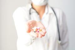 显示几个片剂和药片在她的棕榈的一位女性医生的播种的射击 免版税库存照片