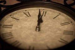 显示分钟的古色古香的生铁时钟对午夜 库存图片