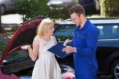 显示剪贴板的技工对恼怒的妇女乘故障汽车 库存照片