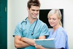 显示剪贴板的年轻女性护士对男性狩医 免版税库存图片