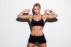 显示力量的一个美丽的肌肉女运动员的画象 免版税库存图片