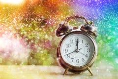显示午夜的闹钟在与五颜六色的抽象bokeh的新年或圣诞节 库存照片