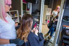 显示发型照片的妇女在智能手机对美发师 库存照片