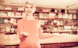 显示各种各样的家庭纺织品的成熟妇女卖主 免版税图库摄影