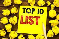 显示名列前茅10十的文字文本列出在稠粘的便条纸写的成功十名单的企业概念,与f的木背景 免版税图库摄影