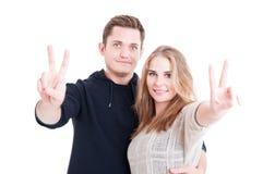 显示和平姿态的愉快的英俊的夫妇 免版税图库摄影