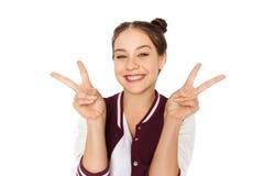 显示和平标志的愉快的微笑的十几岁的女孩 图库摄影