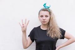 显示四个手指的女孩  图库摄影