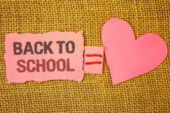 显示回到学校的文本标志 概念性照片回归到类第一天研究教室到达的文本桃红色被撕毁的笔记equ 免版税库存图片