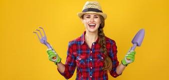 显示园艺工具的微笑的现代妇女农夫 库存照片
