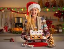 显示圣诞节曲奇饼房子的圣诞老人帽子的女孩 免版税库存图片