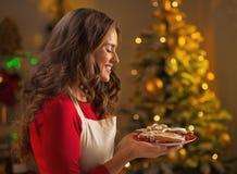 显示圣诞节曲奇饼的愉快的年轻主妇 免版税库存图片