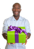 显示圣诞节的笑的非洲人一件礼物 库存照片