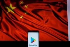 显示在中国旗子前面的谷歌戏剧商店商标的机器人智能手机 免版税库存照片