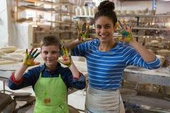 显示在他们的手上的母亲和儿子五颜六色的油漆 库存图片