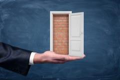 显示在商人` s棕榈站立的砖墙的一个小白色门名望开头 库存照片