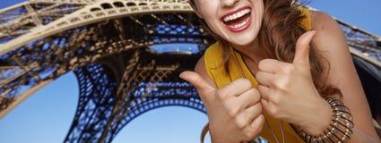 显示在埃佛尔铁塔前面的微笑的少妇赞许 免版税库存图片