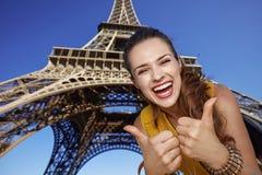 显示在埃佛尔铁塔前面的微笑的少妇赞许 库存图片