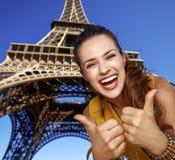 显示在埃佛尔铁塔前面的微笑的少妇赞许 免版税库存照片