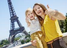 显示在埃佛尔铁塔前面的母亲和孩子赞许 库存照片