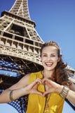 显示在埃佛尔铁塔,巴黎前面的妇女心形的手 库存照片