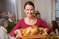 显示在她的家庭前面的俏丽的妇女烘烤火鸡 库存图片