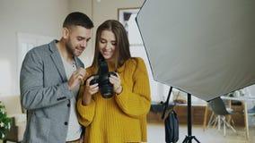 显示在数字照相机的专业摄影师人照片对美丽的式样女孩在照片演播室户内 免版税图库摄影