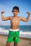 显示在海滩的小男孩肌肉 免版税库存照片