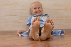 显示在照相机的微笑的女孩脚 免版税库存照片
