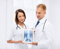 显示在片剂个人计算机的两位医生X-射线 库存照片