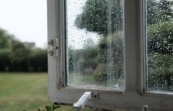 显示在玻璃的被打开的木被构筑的窗口水滴 图库摄影