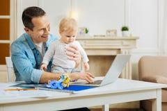 显示在膝上型计算机的快乐的父亲一场比赛,当抱着他的婴孩时 库存图片