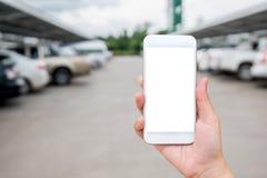 显示在被弄脏的汽车的妇女手巧妙的电话在停车场 免版税库存照片