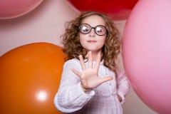 显示在backg的一位少年女小学生的画象五个手指 免版税图库摄影