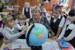 显示地球的成熟老师对孩子 库存图片