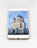 显示塔林的整个银幕的图片现代智能手机, Est 免版税库存照片