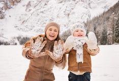 显示多雪的手套的母亲和孩子在冬天户外 免版税图库摄影