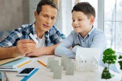 显示太阳电池板模型的年轻工程师对他的儿子 库存照片