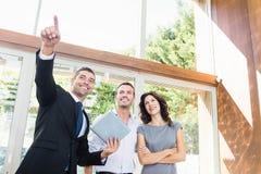显示夫妇新的家的房地产经纪人 免版税库存照片